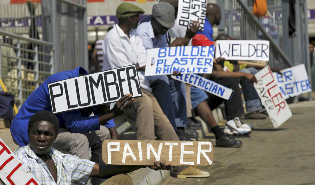 Men hold placards offering temporal employment services in Glenvista, south of Johannesburg